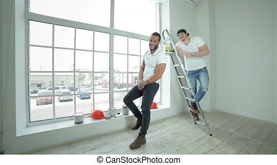 Two young builders standing at the ladder - Good job.Two...