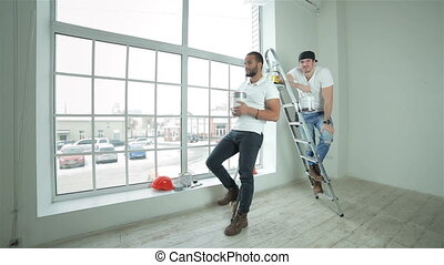 Two young builders standing showing thumbs up - Moving and...