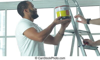 Two workers make repairs in a new apartment - Painting,...