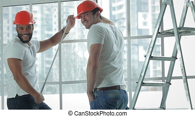 Two workers make repairs in a new apartment - Building,...