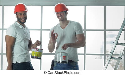 Two workers wearing helmets show okay - Construction, repair...