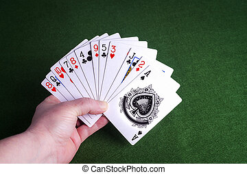 Male hand holding pack of cards on green felt background