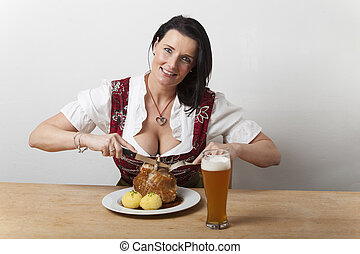 bavarian woman in a dirndl with pork