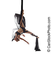 Aerial silks. Flexible dancer posing upside down, isolated...