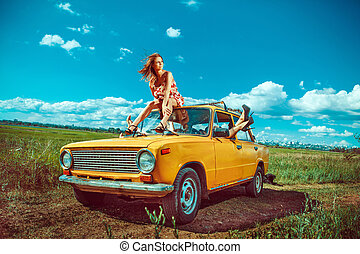 Group of beautiful women in the old yellow car. Green fields...