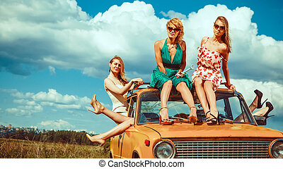 Five beautiful women on the old car. Green fields and blue...