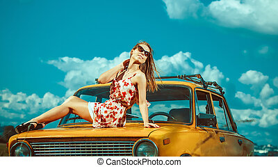 Beautiful woman is laying on the old car