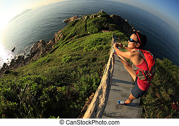 young fitness woman trail runner stretching legs on sunrise...