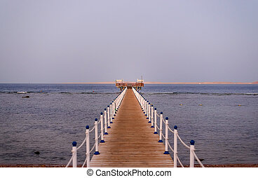 Wooden jetty off a tropical beach leading away from the...