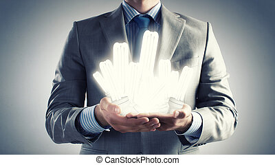 Save energy - Close up of businessman hands holding glass...