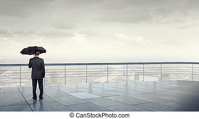 Man with black umbrella - Back view of businessman with...