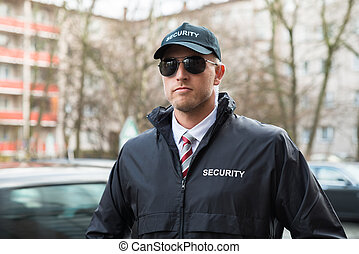 Portrait Of Young Security Guard Wearing Black Uniform And...