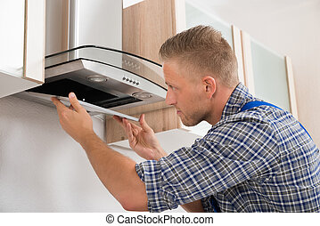 Repairman Repairing Kitchen Extractor Filter - Young...
