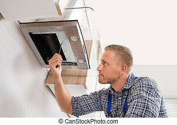 Worker Fixing Kitchen Hood