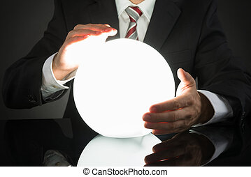 Businessman Predicting Future With Crystal Ball - Close-up...