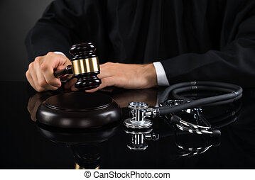 Close-up Of Judge Hitting Gavel With Stethoscope - Close-up...