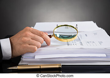 Businessperson Hands Analyzing Receipt With Magnifying Glass...
