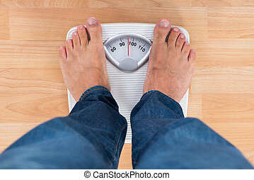 Man Standing On Weighing Scale - Low Section Of Man Standing...