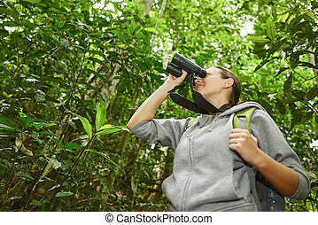 hiker watching through binoculars wild birds in the jungle....