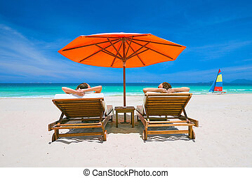 Couple on a tropical beach on deck chairs under a red...