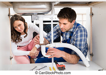Woman Looking At Worker Fixing Pipe - Young Woman Looking At...
