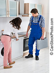 Woman Showing Dishwasher To Worker - Young Woman Showing...
