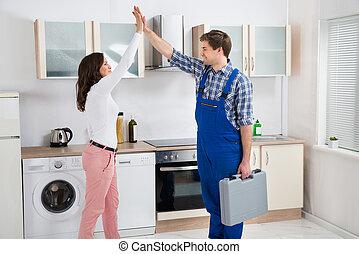 Woman Giving High Five To Repairman - Young Woman Giving...