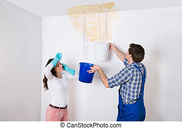 Woman With Worker Collecting Water From Ceiling In Bucket -...