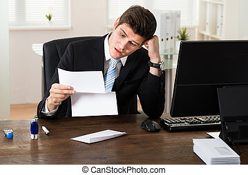 Shocked Businessman With Document In Office - Portrait Of...