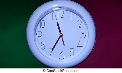 close up of an office clock on colorful background slow...
