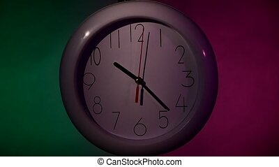 Clock on color wooden plank wall, night. slow motion