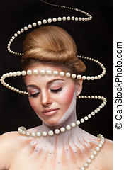 Surreal art concept of girl with pearls arround her. Studio...