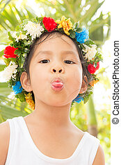 little girl with sticking out tongue on green leaves...