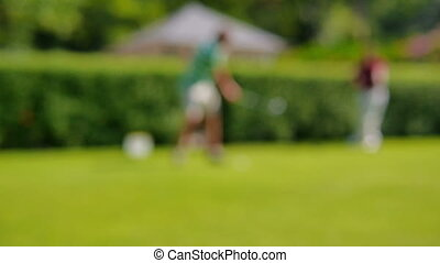Blurred view of people playing golf - Two people playing...