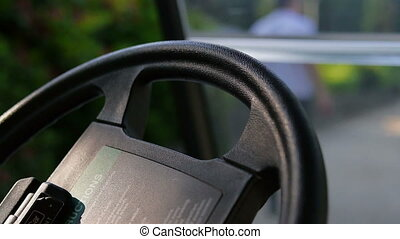 Close up of a black steering wheel in a golf car. In the...
