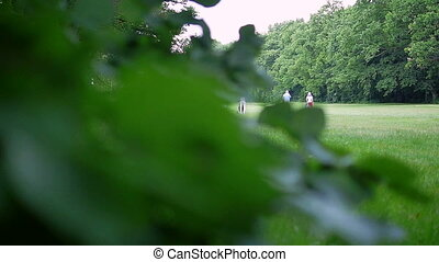 Four people at a golf course Camera is focused on the...
