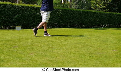 Man in shorts playing a drive