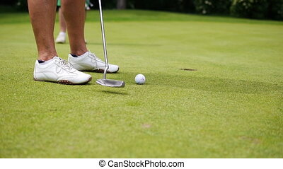 Man is playing a putt - Two men standing at a a golf course...