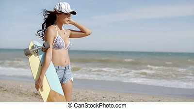 Sporty young woman carrying a skateboard as she strides...