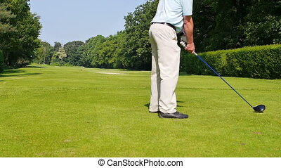 Man playing a drive on a golf course - A man is playing a...