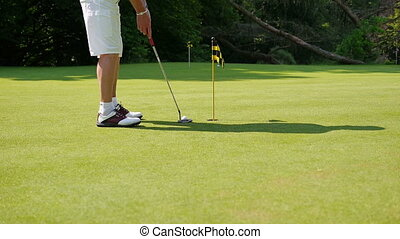 Man playing a putt on a sunny day - A man dressed in shorts...