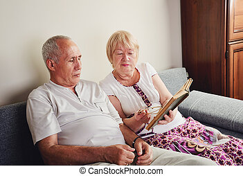 older man and woman 60-65 years old sitting on the sofa and...
