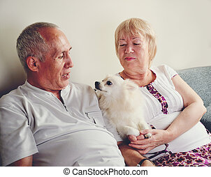 mature man and woman 60-65 years old sitting on the sofa and...