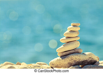 Stones balance at the beach, stack over blue sea - Stones...