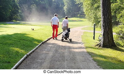 Two men walking down a sand path with to the next hole