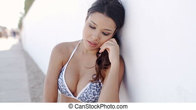 Pensive young woman leaning against a wall