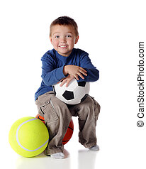 Sports Lover - A happy preschooler sitting with three...