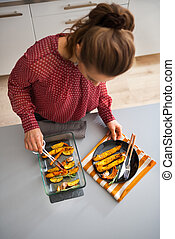 Seen from above, woman serving roasted autumn vegetables -...