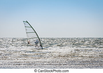 windsurfer riding the waves in an empty sea