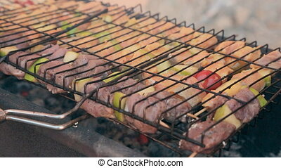 Different kinds of meat grilled on a barbecue outdoors -...
